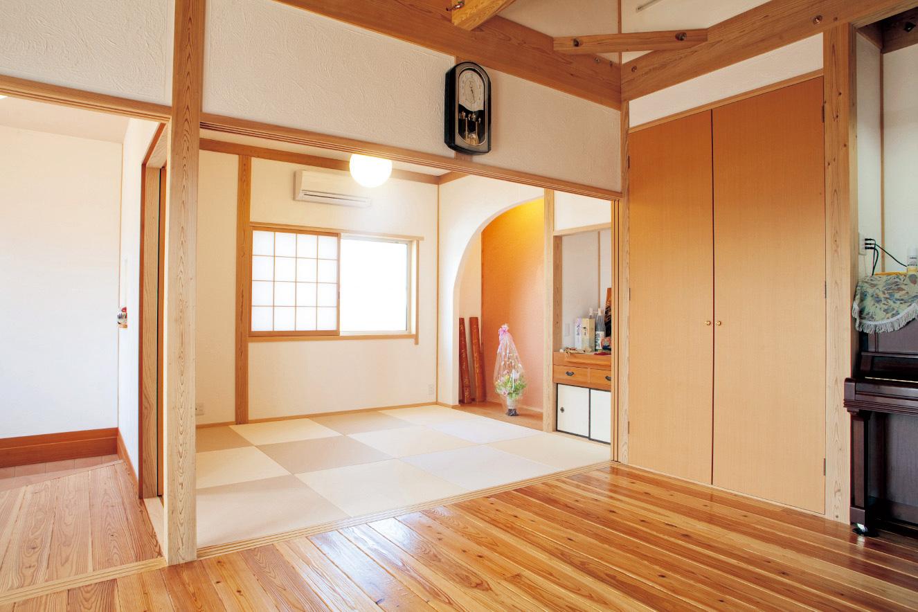 ベージュの畳で市松模様にした和室。その色づかいと床の間のアールの曲線が優しげな雰囲気を演出する。床の間の下には隠し収納がある
