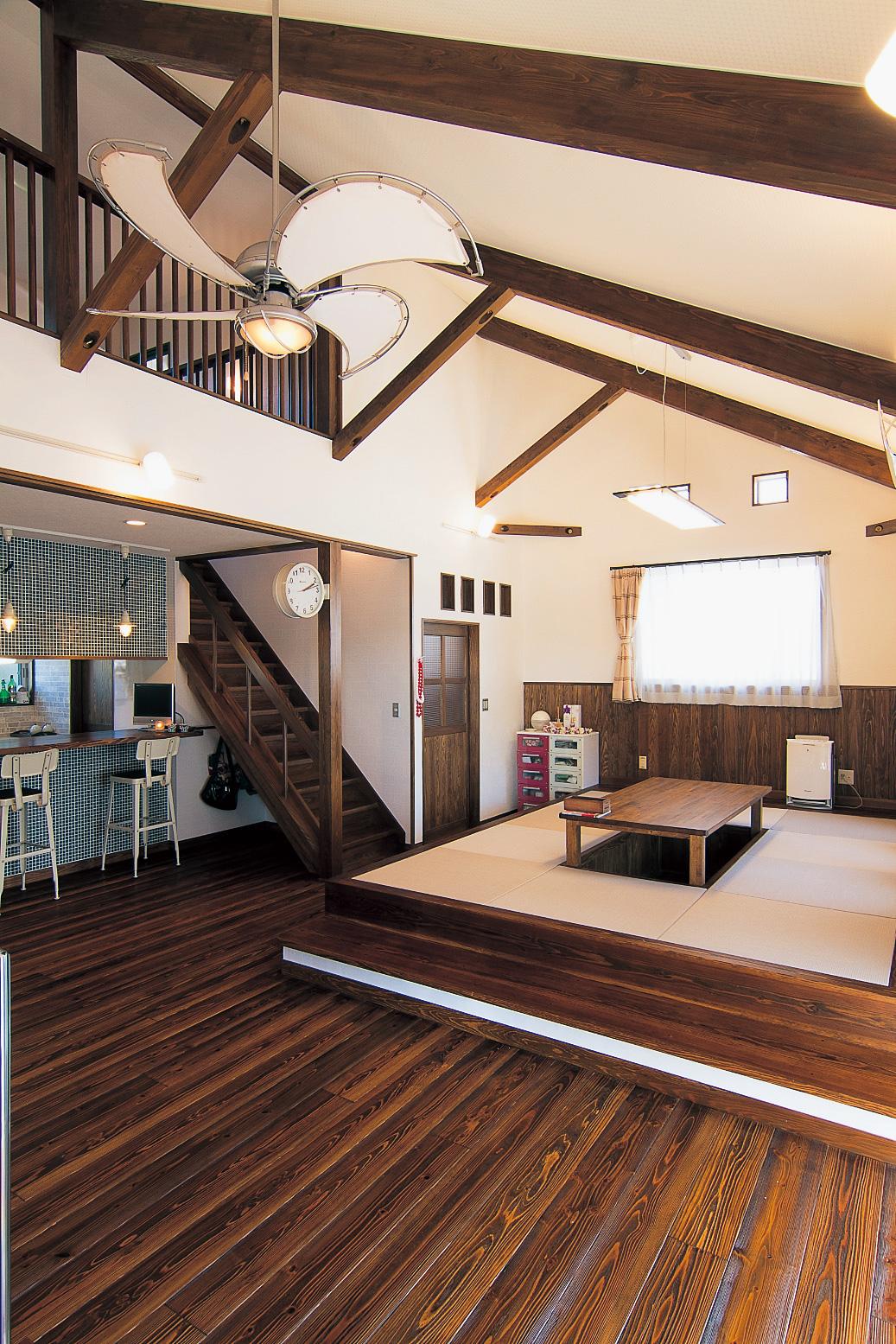 リビングのポイントは、片流れの大きな屋根の勾配を活かした吹き抜け。漆喰壁と飴色の木肌に、ご夫婦の好きなダルトン社製のアメリカン家具や雑貨がよく映える