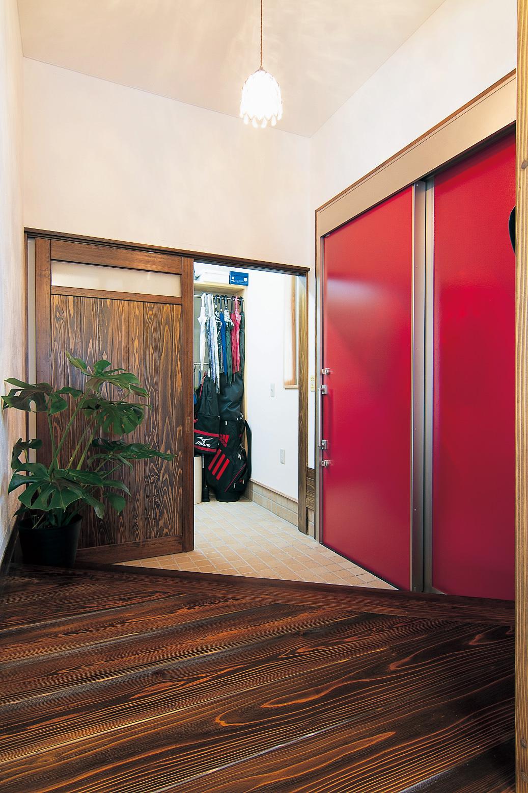 真っ赤なスライドドアが印象的な玄関。ウォークインシューズクロークを通って、直接キッチンへも行ける。ドアの向こうはガレージで濡れずにで切りできて便利