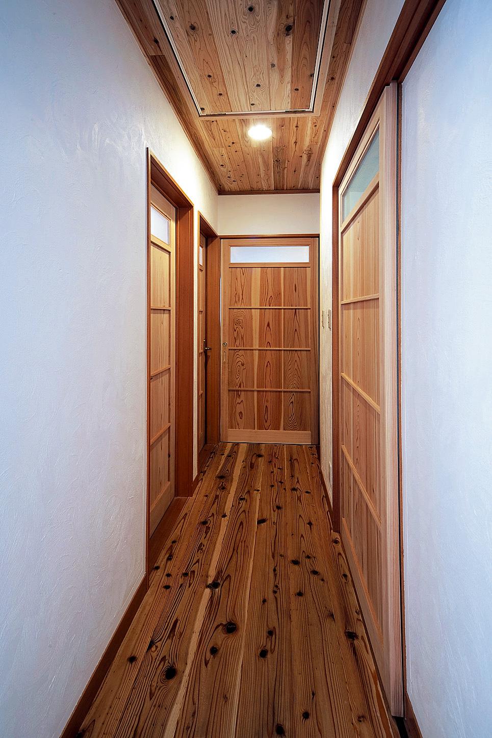 間接照明が照らす廊下もナチュラル感がいっぱい。左に並ぶのは子供部屋の入り口。右は浴室、奥がトイレ