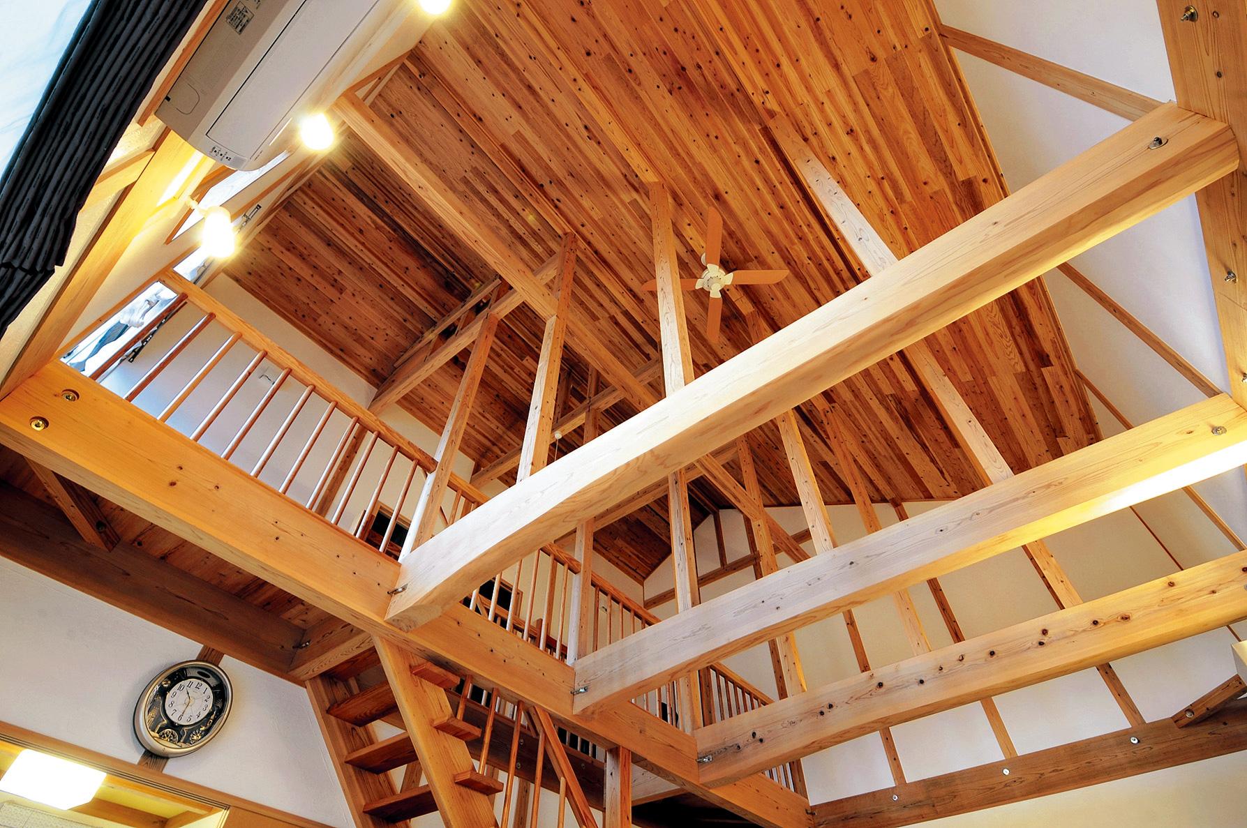 吹き抜けに見せた梁は空間を個性づけるデザインの役割も。立派な杉の一枚板をはじめ木材をふんだんに生かした造りは、製材も行う同社ならでは