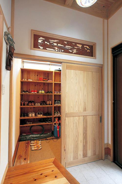 玄関の土間収納は容量たっぷり。味わいのある欄間は、装飾だけでなく本来持つ採光・通気の役割も担っています。